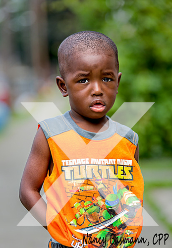 Little boy in the street wearing a ninja turtle shirt